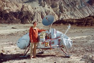 Carl Sagan poses with a model of the Viking lander in Death Valley